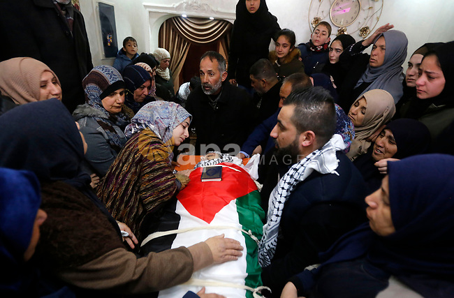 Relatives of Palestinian Hamza Zamareh mourn over his body during hid funeral in Halhoul, in the West Bank city of Hebron on February 17, 2018. Hamza stabbed a security guard at the entrance of the Israeli settlement Karmei Tzur north of Hebron and was shot dead, the Israeli army said, in the latest violence in the occupied West Bank. Photo by Wisam Hashlamoun