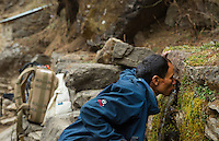 Nepal Nepali man drinking from public water fountain along trail in Solukhumbu remote near Mt Everest  50