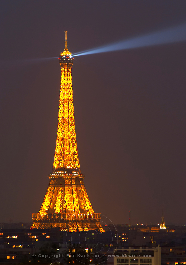 The Eiffel Tower in Paris illuminated at night against a dark blue black sky, search light ray on the sky, illumination golden yellow Paris France