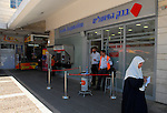 Israelis and a Bank hapoalim branch at a commercial center in north Jerusalem.<br />