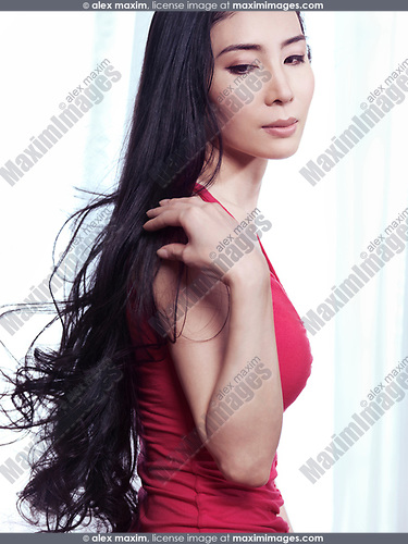 Beauty portrait of a young Japanese woman with long black hair at a brightly lit window