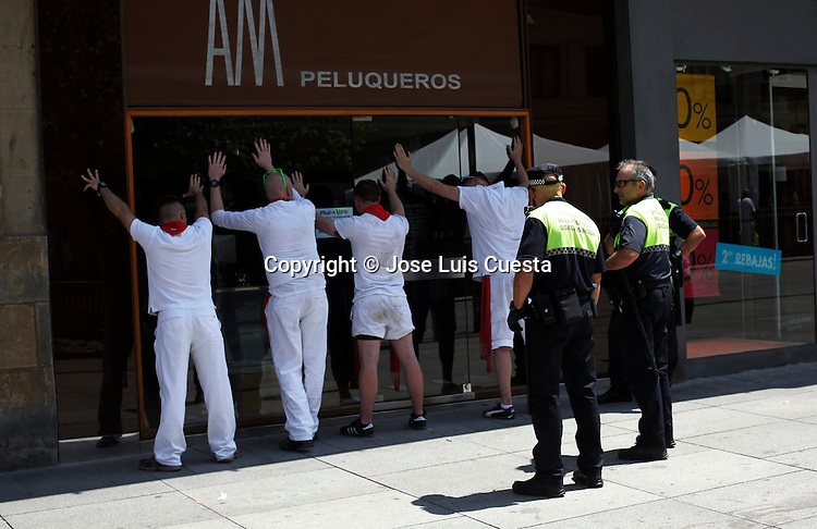 Some revelers are arrested at the street by police. San Fermin festival is worldwide known because the daily running bulls.