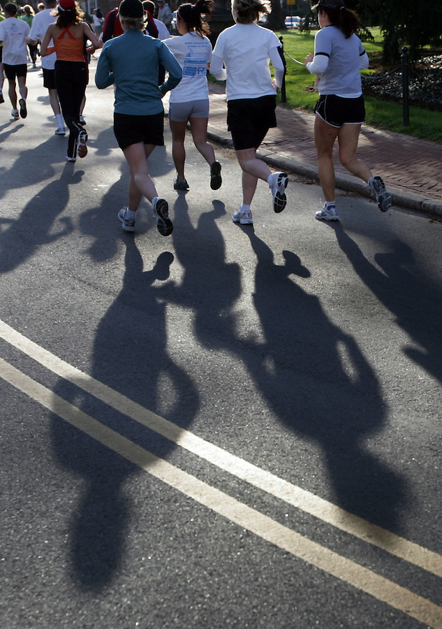Shodows follow closely behind runner as they make their way by the University Chapel during the Charlottesville 10-miler Saturday in Charlottesville, Va. Photo/Andrew Shurtleff