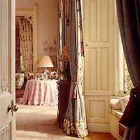 Floor to ceiling curtains decorate the windows, their gold braid mirroring the gilded carving on the Victorian shutters