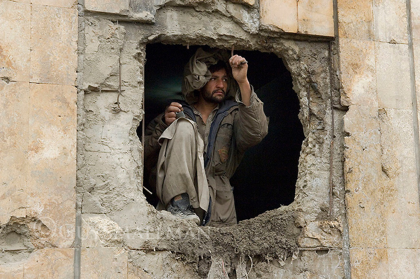 Russian Cultural Palace Kabul. The building was destroyed by the Mujahadeen during the Afghan civil war. Hundreds of people use the building to smoke and inject heroin. The Welfare Association for the Development of Afghanistan (WADAN) has reclaimed part of the building and turned it into a rehabilitation clinic. Addict looks out through a blast hole in the building.