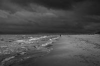 ensam man promenerar på en sandstrand vid havet med mörka moln på Östelen i Skåne Svartvitt