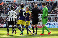 Pictured: Wayne Routledge of Swansea (C) squares up against goalkeeper Tim Krul of Newcastle (R). Saturday 19 April 2014<br />