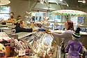 Deli worker handing a customer a package in the meat department