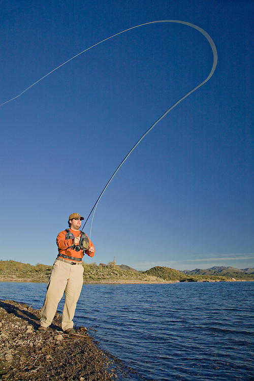Man casts his fly fishing line into Lake Pleasant in Arizona