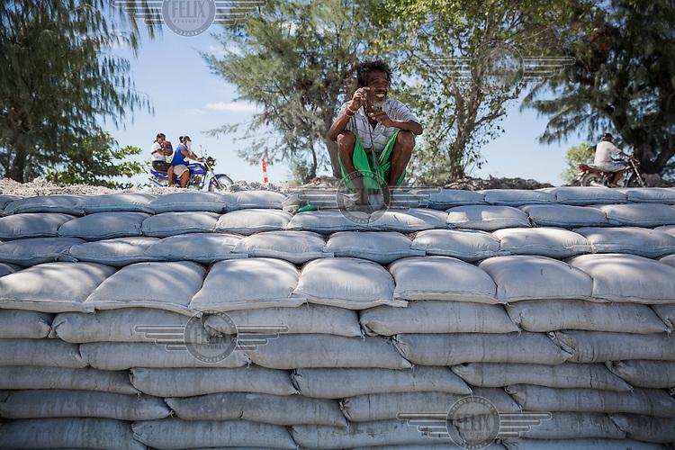 Makaua, 40, sits on the sea wall at Teaoraereke village near Bairiki town. The Kiribati government build seawalls in most of South Tarawa, but despite their efforts, many of the walls get damaged by big waves.
