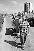"""Two men move a piano along Sarajevo's notorious """"Sniper Alley"""" on August 30 1994, while a French United Nations armoured vehicle drives past."""