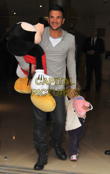PETER ANDRE & PRINCESS TIAAMII ANDRE .Leaving The Mayfair Hotel with a large Mickey Mouse toy, London, England, UK, 28th January 2010..full length family father dad holding hands grey gray top trousers tucked into boots purple white cream knitted jacket cardigan .CAP/DYL.©Dylan/Capital Pictures.