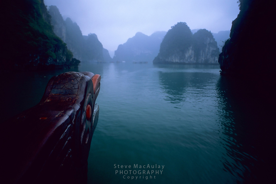 View from bow of traditional Vietnamese junk as it sails through a narrow passage in Ha Long Bay, Vietnam