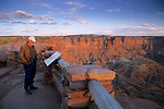 Tourist reading interpretive panel at the Green River Overlook, Island in the Sky, Canyonlands National Park, UTAH
