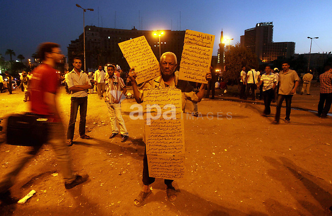 An Egyptian protester holds slogans against presidential candidates Mohammed Morsi and Ahmed Shafiq at Tahrir Square in Cairo May 29, 2012. According to full official results released Monday by the election commission. Commission chief Farouq Sultan said in a press conference that the Brotherhood's Mohammed Morsi and Ahmed Shafiq, a former air force commander and a longtime friend of the ousted leader, were the top two finishers in the first round of voting held on May 23-24. Photo by Ashraf Amra