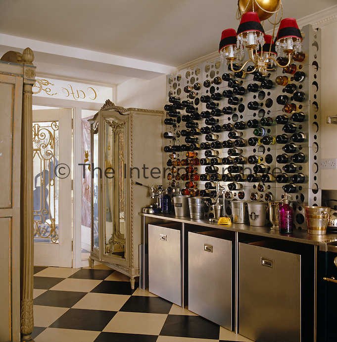 Contemporary stainless steel wine rack above a kitchen unit with large storage bins