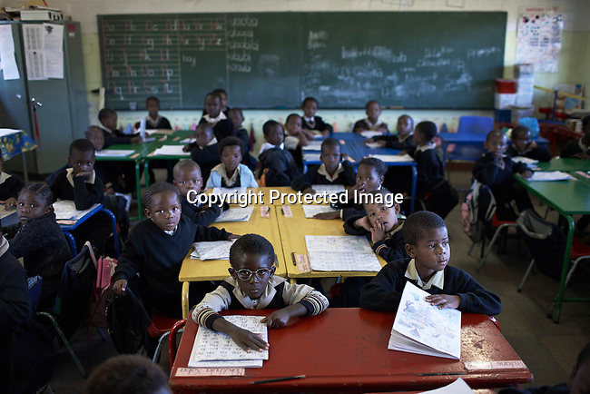 SOWETO, SOUTH - AFRICA MAY 10: Primary school children listens to their teacher during an English class on May 10, 2007 in Orlando West district of Soweto, South Africa. Many of the children are poor and live with usually one parent or with grandparents. The school provides a free meal every day, and the food is the only meal for some of the poorest children. Soweto is South Africa's largest township and it was founded about one hundred years to make housing available for black people south west of downtown Johannesburg. The estimated population is between 2-3 million. Many key events during the Apartheid struggle unfolded here, and the most known is the student uprisings in June 1976, where thousands of students took to the streets to protest after being forced to study the Afrikaans language at school. Soweto today is a mix of old housing and newly constructed townhouses. A new hungry black middle-class is growing steadily. Many residents work in Johannesburg, but the last years many shopping malls have been built, and people are starting to spend their money in Soweto. (Photo by Per-Anders Pettersson)