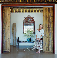 Portrait of Charlene de Ganay standing in the entrance to her beach house