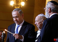 Il Primo Ministro israeliano Benjamin Netanyahu, affiancato dal reduce dai lager nazisti Mario Limentani, al centro, e dal Rabbino Capo di Roma Riccardo Di Segni, a destra, accende una candela durante la cerimonia per l'inizio della Festa ebraica delle Luci di Chanukkah, al termine dell'incontro la Comunita' Ebraica romana insieme al Presidente del Consiglio nel Tempio Maggiore, Roma, 1 dicembre 2013.<br /> Israeli Prime Minister Benjamin Netanyahu, flanked by survivor from the Holocaust Mario Limentani, center, and Rome's Chief Rabbi Riccardo Di Segni, right, lights a candle to mark the start of the Jewish light festival of Hanukkah, as he meet the Roman Jewish Community with the Italian Premier at the Great Synagogue, Rome, 1 December 2013.<br /> UPDATE IMAGES PRESS/Isabella Bonotto