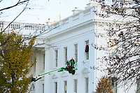 A worker hangs Christmas wreaths on the White House windows
