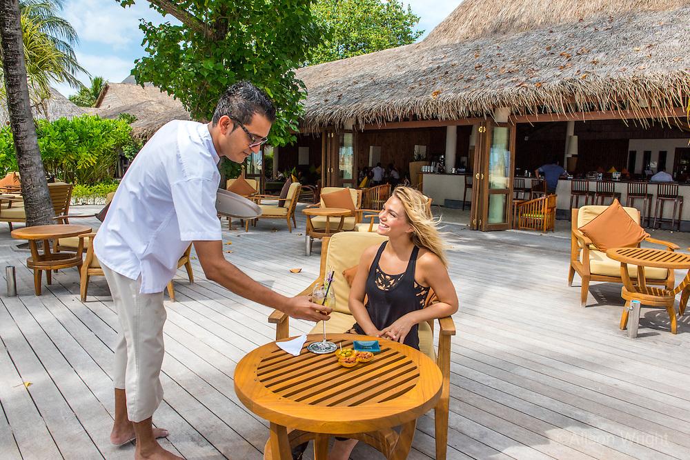 Maldives, Rangali Island. Conrad Hilton Resort. Woman having a drink at the resort (MR).