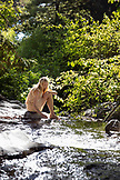 USA, California, Big Sur, Esalen, a woman sits by Hot Springs Creek at the Esalen Institute