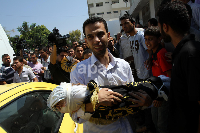 A Palestinian man carries the body of two-year-old boy Islam Qreqa during a funeral in Gaza City on August 20, 2011. Palestinians said at least nine militants have died in multiple Israeli strikes, as well as two children, one of them Islam Qreqa. Photo by Mohammed Asad