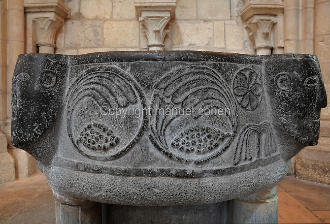 Baptismal font, 11th century, in black Tournai stone, with 4 faces representing either the Evangelists, or the 4 Rivers of Paradise (Tigris, Euphrates, Gihon and Pison) and carved symbols of life, in the South transept, Laon Cathedral or the Cathedrale Notre-Dame de Laon, built 12th and 13th centuries in Gothic style, in Laon, Aisne, Picardy, France. The cathedral is listed as a historic monument. Picture by Manuel Cohen.