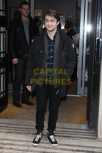 Daniel Radcliffe at the studios of BBC Radio 2, London, England..February 10th, 2012.full length black jeans denim coat jacket grey gray hands in pockets green check shirt sneakers trainers .CAP/HIL.©John Hillcoat/Capital Pictures .