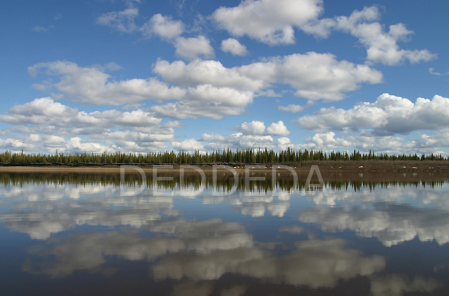 Cloud reflections on the Porcupine River near Old Crow, Yukon Territory, Canada..