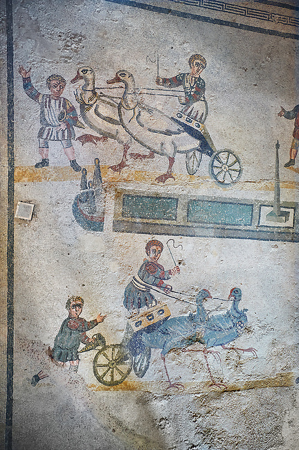wide shot of the Roman mosaics of the room of the Small Circus depicting Roman boys riding small chariots pulled by birds in a small circus, The Vestibule of The Smnall Circus, room no 41  at the Villa Romana del Casale, first quarter of the 4th century AD. Sicily, Italy. A UNESCO World Heritage Site.<br /> <br /> The Roman mosaic know as the Small Circus at the Villa Romana del Casale depicts a scene of a chariot race from the Circus Maximus in Rome. Two wheeled chariots, driven by children,  are racing around a central Pina (barrier) being drawn by fowl and web footed birds. The four chariots represent the four factions that raced against each other at the Circus and the tunics of the cild charioteers and the birds pulling their chariots are distinguished by the four different colours used by each faction.