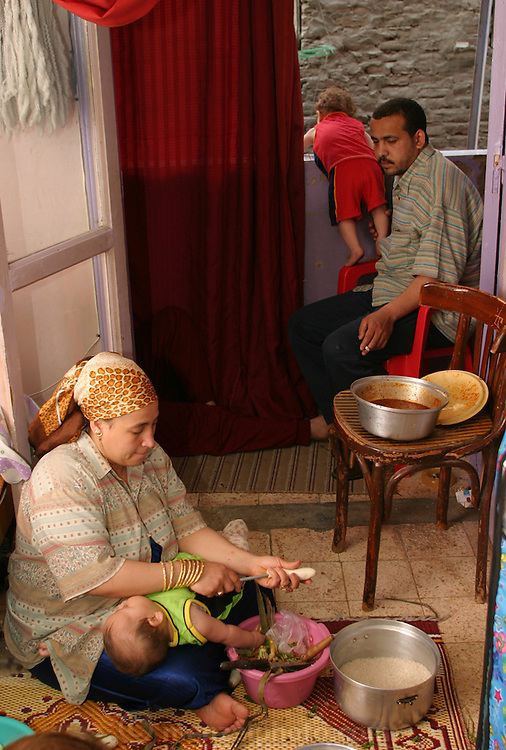 (MODEL RELEASED IMAGE). Nadia Mohamed Ahmed, 36, makes mahshi (stuffed food, in this case small eggplants) on the floor of her fourth-floor apartment. Heedless of the activity, baby Nancy sleeps on Nadia's lap; meanwhile, her brother and nephew sit on the balcony overlooking the narrow street. (Supporting image from the project Hungry Planet: What the World Eats.)