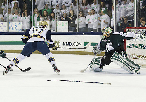December 07, 2012:  Notre Dame right wing Austin Wuthrich (#27) shoots the puck as Michigan State goaltender Jake Hildebrand (#30) looks to make the save during NCAA Hockey game action between the Notre Dame Fighting Irish and the Michigan State Spartans at Compton Family Ice Arena in South Bend, Indiana.  Notre Dame defeated Michigan State 3-2.