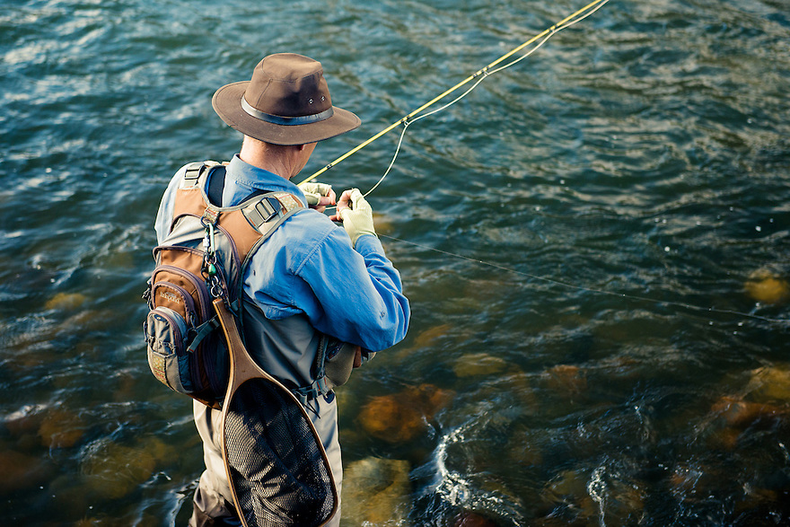 An angler ties on a caddis pattern during the Mother's Day caddis hatch on the Madison River.