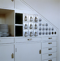 Functional drawers and circular storage bins above some built-in cupboards and drawers in the white-painted fitted kitchen