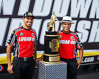 Sep 18, 2016; Concord, NC, USA; NHRA pro stock motorcycle riders Hector Arana Jr (left) and father Hector Arana Sr pose next to the championship trophy during the Carolina Nationals at zMax Dragway. Mandatory Credit: Mark J. Rebilas-USA TODAY Sports