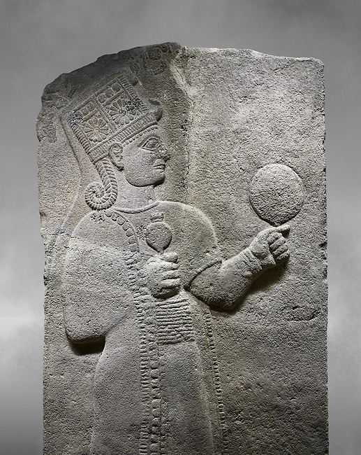 Hittite relief sculpted orthostat stone panel of Long Wall Basalt, Karkamıs, (Kargamıs), Carchemish (Karkemish), 900 - 700 B.C. Anatolian Civilizations Museum, Ankara, Turkey.<br /> <br /> Goddess Kubaba. Goddess is depicted from the profile. The part below the chest of the relief is broken. She holds a pomegranate in her hands on her chest. She carries a one-horned headdress on her head. Her braided hair hangs down to her shoulder. The text in the hieroglyphics is not understood. The lower part of the relief has been restored. <br /> <br /> On a grey art background.