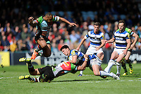 Ollie Devoto of Bath Rugby is tackled by Maurie Fa'asavalu of Harlequins as Jordan Turner-Hall of Harlequins jumps over during the Aviva Premiership match between Harlequins and Bath Rugby at The Twickenham Stoop on Saturday 10th May 2014 (Photo by Rob Munro)