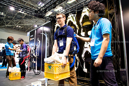"""A visitor carries a heavy box using the """"Wearable Robot Muscle Suit"""" at the Japan Robot Week 2014 on October 16, 2014 in Tokyo, Japan. Companies at the """"Japan Robot Week 2014"""" exhibited their latest high-tech nursing and life supporting robots. The 2014 edition of the show ran from October 15 to 19 at Tokyo Big Sight. (Photo by Rodrigo Reyes Marin/AFLO)"""