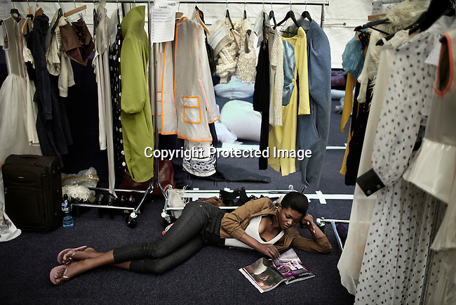 JOHANNESBURG, SOUTH AFRICA SEPTEMBER 22: A models reads a fashion magazine backstage before a fashion show at South Africa Fashion Week on September 22, 2011 held in Johannesburg, South Africa. Designers showed their spring/summer collections. (Photo by: Per-Anders Pettersson)