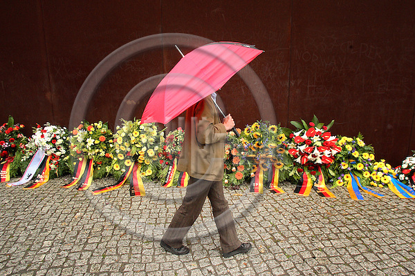 BERLIN - GERMANY 13.  AUGUST 2006 -- At the 45th Anniversary of the Construction of the Berlin Wall, A man is walking by the flowers at the formal Berlin Wall Memorial at Bernauer Strasse -- PHOTO: UFFE Noejgaard/ EUP-IMAGES