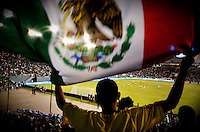 A Mexico fan waves a Mexican flag in an exhibition game against Colombia at the Cotton Bowl in Dallas, Texas, USA, Wednesday, Sept., 30, 2009. Colombia won the game 2-1, which was played as the second game of a double header after an FC Dallas soccer game in an attempt by Major League Soccer to draw a new crowd of hispanic people to the sport in the US...PHOTOS/ MATT NAGER