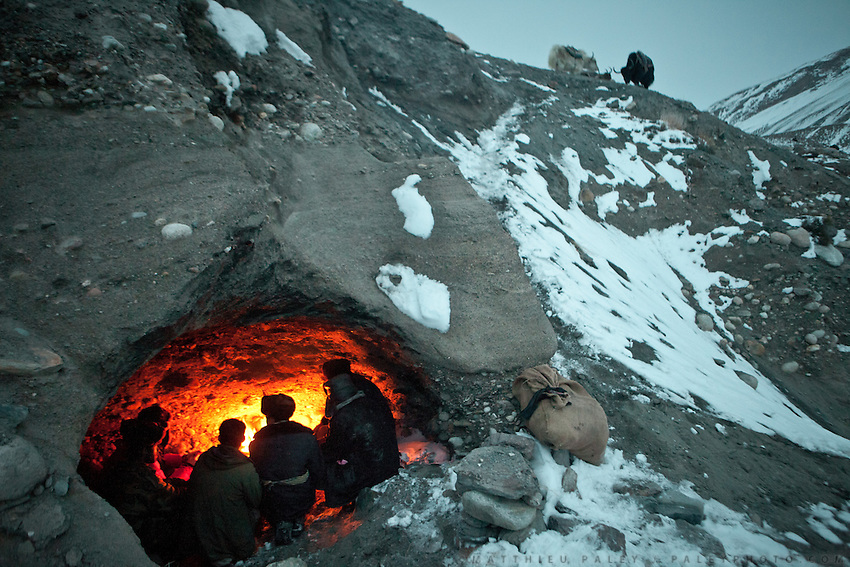 Kyrgyz men seek shelter in a shepherd's cave during the icy five-day trek down from their mountainous homeland to the nearest trading village in Afghanistan. They will barter livestock, wool, and dairy products for everything from tea to television sets...In Zan Kuk. .Trekking back down from the Little Pamir, with yak caravan, over the frozen Wakhan river.