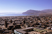 Puno, Peru. Overview of the town with Lake Titicaca behind; rooftops.