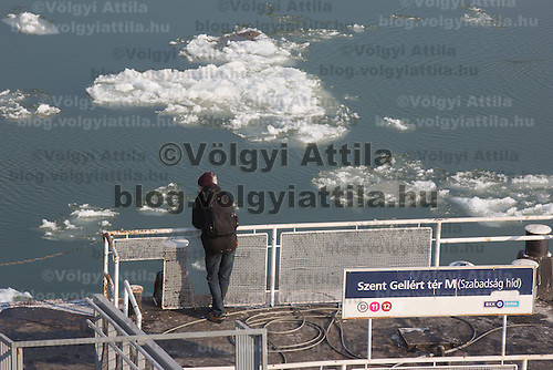 Man watches ice blocks floating on river Danube in Budapest, Hungary on January 10, 2017. ATTILA VOLGYI