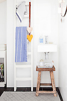 A small but cosy and practical bathroom is furnished with a painted ladder and rustic stool to give it a friendly atmosphere