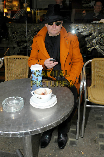George O'Dowd (Boy George) spotted in Soho, London, England..15th February 2012.**EXCLUSIVE ALL-ROUNDER**.full length sunglasses shades black hat orange coat cafe nero cafe coffee drink beverage takeaway sitting table mobile phone scarf.CAP/IA.©Ian Allis/Capital Pictures.