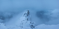 Hiker on summit of Volandstind during clearing winter storm, Flakdstadøy, Lofoten Islands, Norway