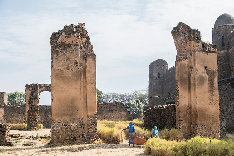 Within the Royal Enclosure containing the castles of Gondar, morning ground's keepers provide a sense of scale for the fallen arch located above them.