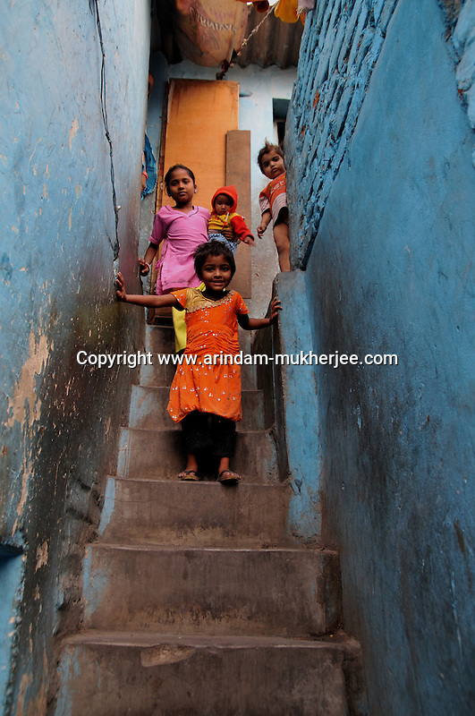 Children at Katputly colony in New Delhi, India. 17.11.2009. Kathputly colony is a slum area in West Delhi. This slum seems like any other slum areas of modern India with dysfunctional electricity, non existing sanitation and poverty. As a part of Delhi, this is also ailed with water crisis. Large families live their lives crammed together in a single room with all the odds which complement poverty. One thing which differentiates this slum with any other is the people living in the colony. Nearly everybody in this slum is a traditional performing artist; and they have been migrating to this area for last 50 years from different parts of the country for a better livelihood. They are magicians, acrobats, jugglers, puppeteers, dancers and musicians. These artistes perform in star rated hotels, marriage ceremonies of the richer section, functions, and festivities all around the country and the world. Most of the artisans I met here, have performed in Europe and America but such opportunities are rare to come by. They struggle to keep their art form alive. They say that they don't get any help or support from the government for their basic needs and for the well being of the Kathputly colony -  though they have uphold the prestige of the country internationally. Polluted air, dirty alleys smelling of urine, colourful dress and sound of music characterise Kathputly colony, which is the one of its kind in India. Arindam Mukherjee